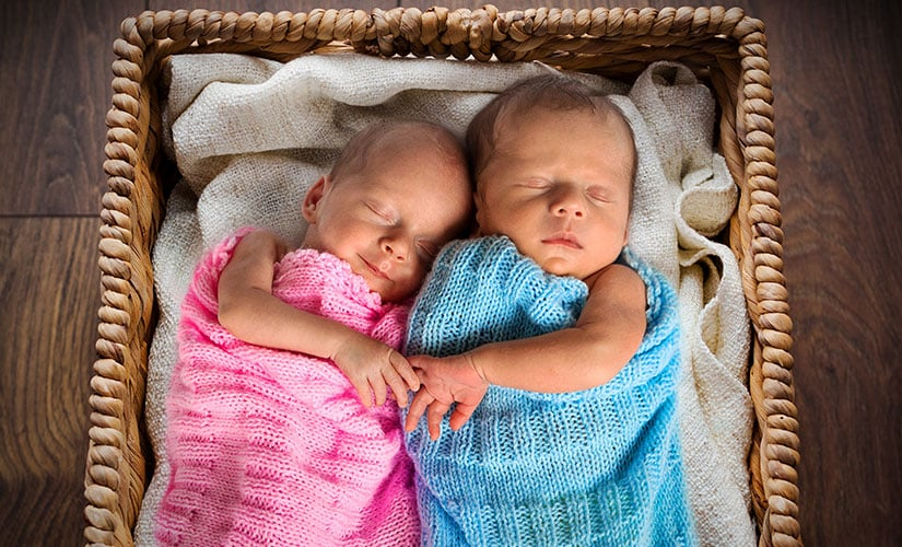 Twins sleeping comfortably in crocheted blanket