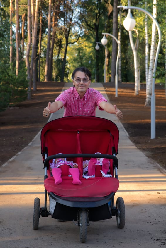 Man jogging with twins in stroller