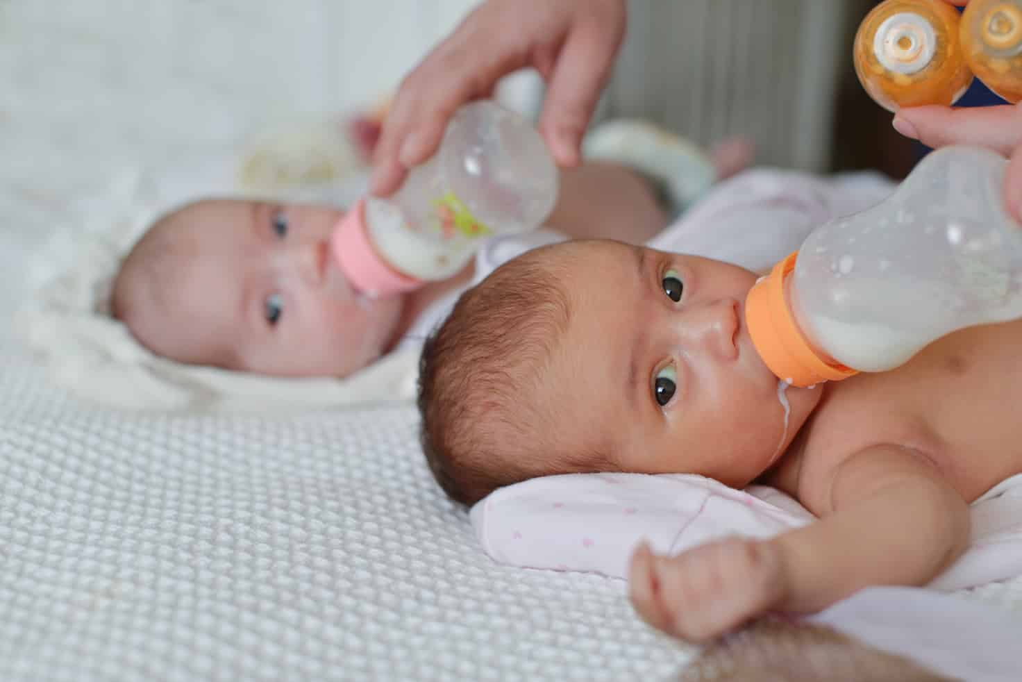twins drinking milk from bottles