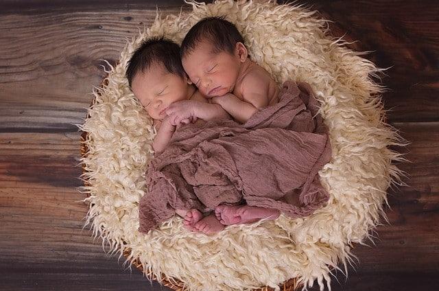Newborn twins cuddling